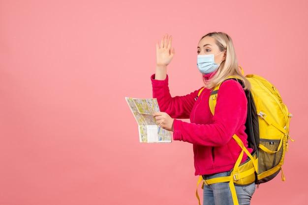 De vrouw van de vooraanzichtreiziger met gele rugzak die masker golvende hand draagt