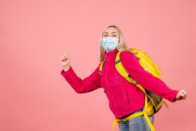 De vrouw van de vooraanzichtreiziger met gele rugzak die masker het lopen dragen