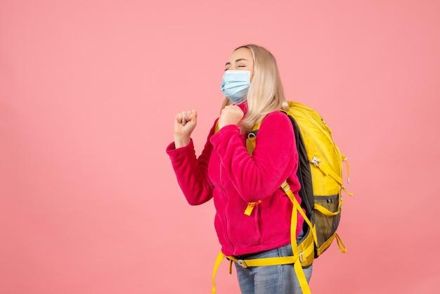 De vrouw van de vooraanzichtreiziger met gele rugzak die masker sluitende ogen draagt