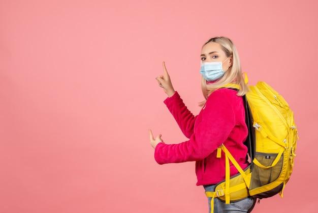 De vrouw van de vooraanzichtreiziger met gele rugzak die medisch masker draagt