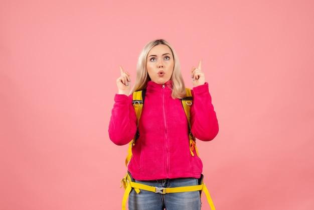 De vrouw van de vooraanzichtreiziger met gele rugzak die met omhoog vingers richt