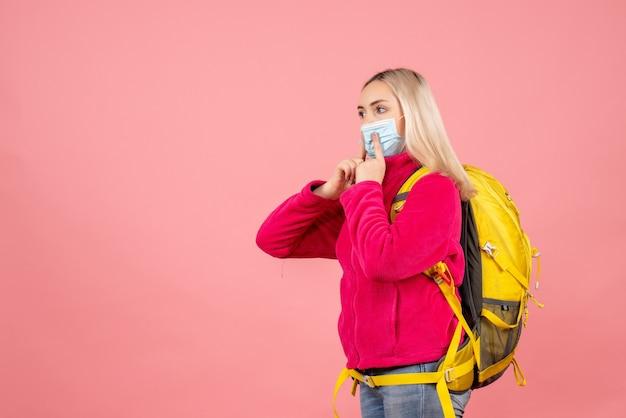 De vrouw van de vooraanzichtreiziger met gele rugzak die op haar masker richt