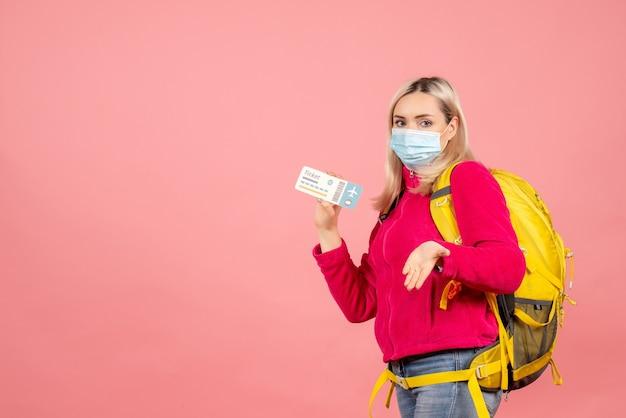 De vrouw van de vooraanzichtreiziger met het kaartje van de maskerholding