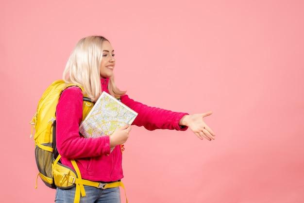 De vrouw van de vooraanzichtreiziger met rugzak die de kaart van de handholding geeft