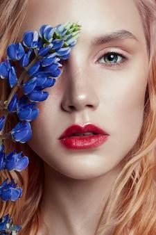 De vrouw van het portretblonde met bloembloemblaadjes op gezicht