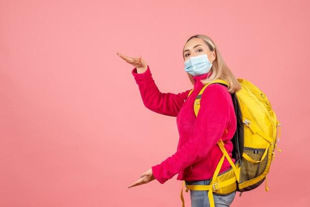 De vrouw van het vooraanzichtblonde met gele rugzak die masker dragen dat grootte met handen toont