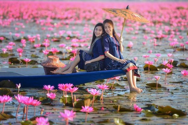 De vrouw van laos in het meer van de bloemlotusbloem, vrouw die traditionele thaise mensen, rode lotus sea udonthani thailand dragen