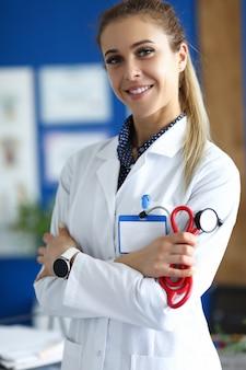 De vrouw van nice arts die zich in het bureau bevindt en een stethoscoop houdt
