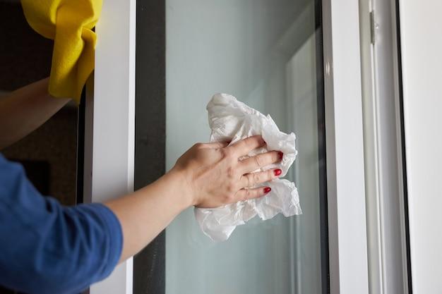 De vrouw veegt een venster af gebruikend een keukenrol