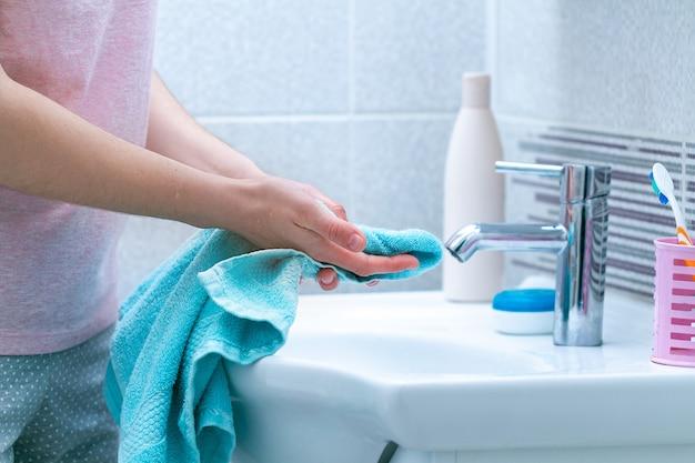 De vrouw veegt handen droog met handdoek na thuis het wassen in badkamers af. hygiëne en handverzorging.