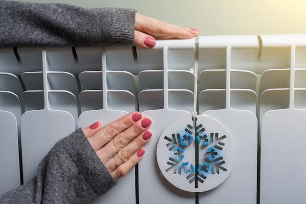 De vrouw verwarmt haar handen op het radiatorpaneel