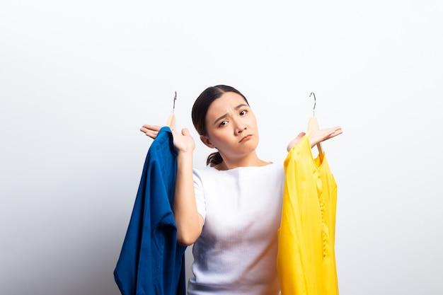 De vrouw voelt verwart aan het kiezen van blouse over witte achtergrond wordt geïsoleerd die