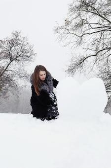 De vrouw vormt een groot hart uit de sneeuw