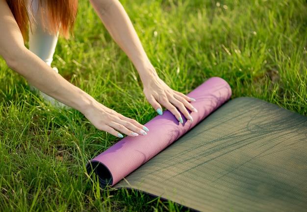 De vrouw vouwt mat na yogatraining dicht omhoog in het park op het gezonde leven