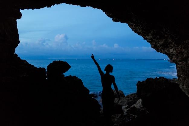 De vrouw wacht zonsondergang in balinessehol bij oceaanstrand.