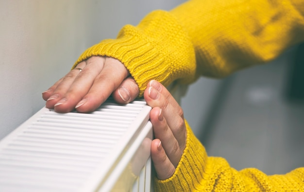 De vrouw warmt haar handen op de radiator