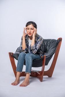 De vrouw was ziek, zat op een stoel en raakte haar hoofd aan met haar hand.