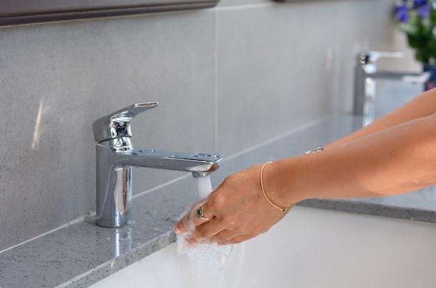 De vrouw wast haar handen bij de gootsteen, het vrouwelijke hand schoonmaken, handenwas
