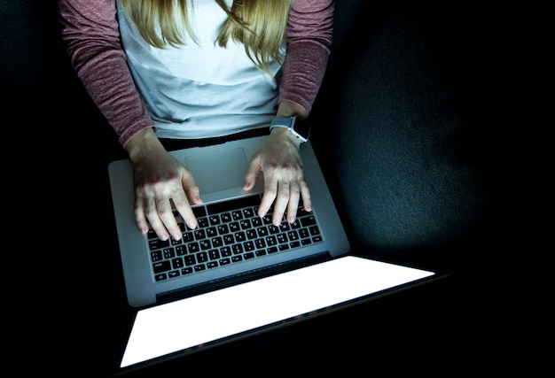 De vrouw werkt laat zittend op bank met laptop