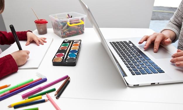 De vrouw werkt met laptop terwijl haar zoon schildert