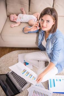 De vrouw werkt thuis terwijl haar kleine baby slaapt.