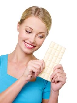 De vrouw wil een tegel zoete witte chocolade eten