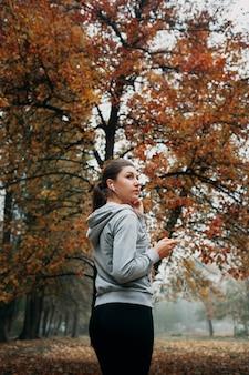 De vrouw zet de muziek aan voor het lopen in het bos