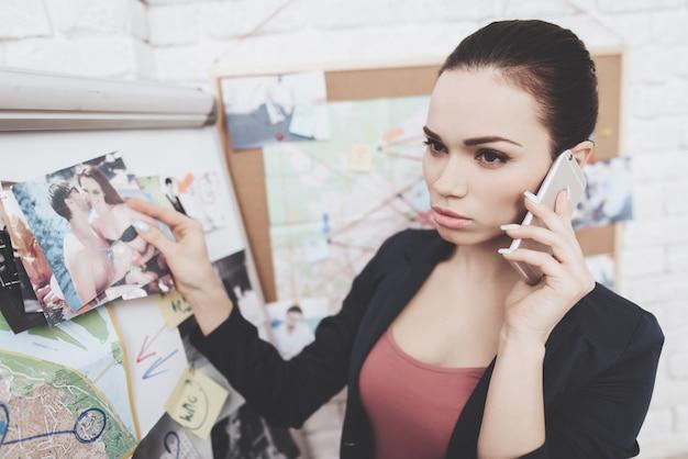 De vrouw zet foto's op aanwijzingskaart in bureau.