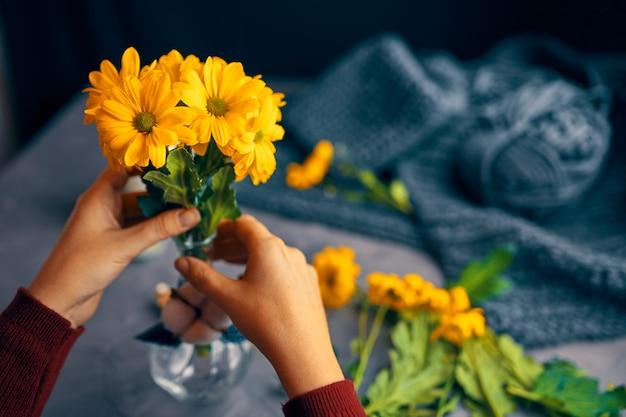 De vrouw zet gele bloemen in vaas