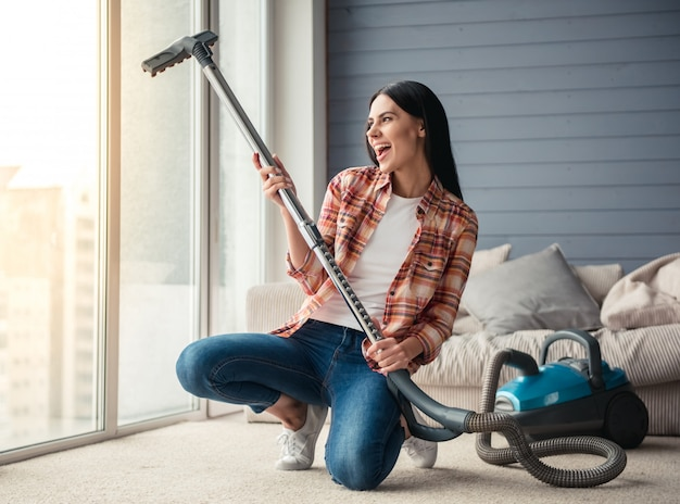 De vrouw zingt en glimlacht terwijl het schoonmaken van vloer