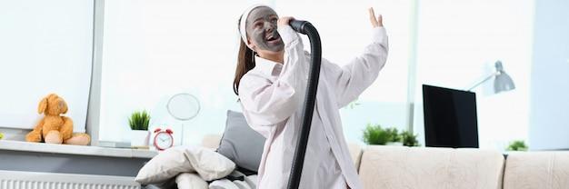 De vrouw zingt lied in stofzuiger tegen modern