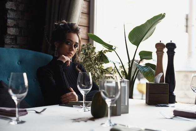 De vrouw zit aan de tafel in café of restaurant en drinkt een koffie