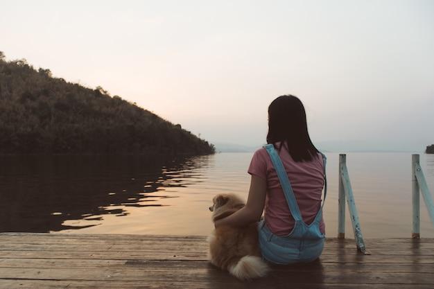 De vrouw zit en ontspant met haar hond bewondert de zonsonderganghemel en het meer.
