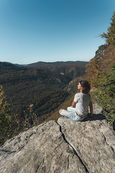 De vrouw zit op een klif en kijkt naar de vallei in de bergen.