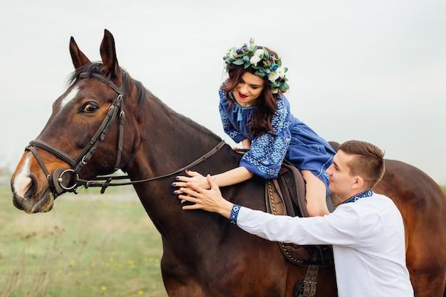 De vrouw zit op een paard en haar vriend staat naast haar en ze aaien samen het paard