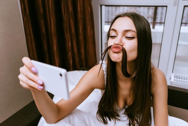 De vrouw zit op het bed en maakt een belachelijke selfie