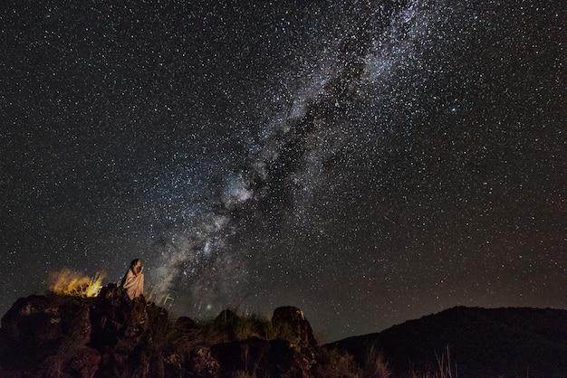 De vrouw zit op steenrichel bekijkend de sterren van de nachthemel met melkachtige manierachtergrond