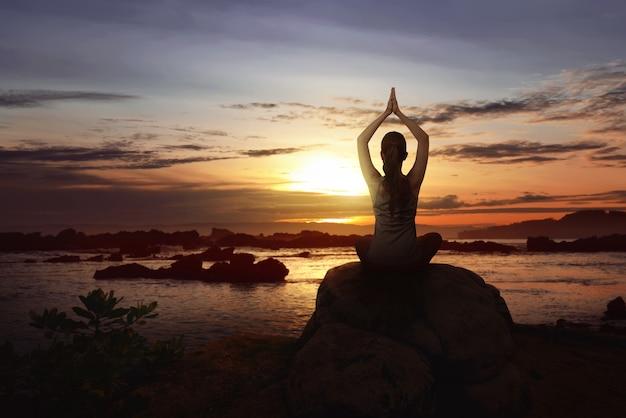 De vrouw zit over de rots die yoga doet
