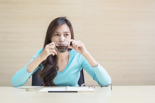De vrouw zit voor het drinken van koffie in transparante kop van koffie met het denken van emotie