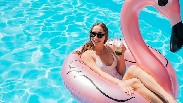 De vrouw zwemt binnen ring die van haar cocktail geniet