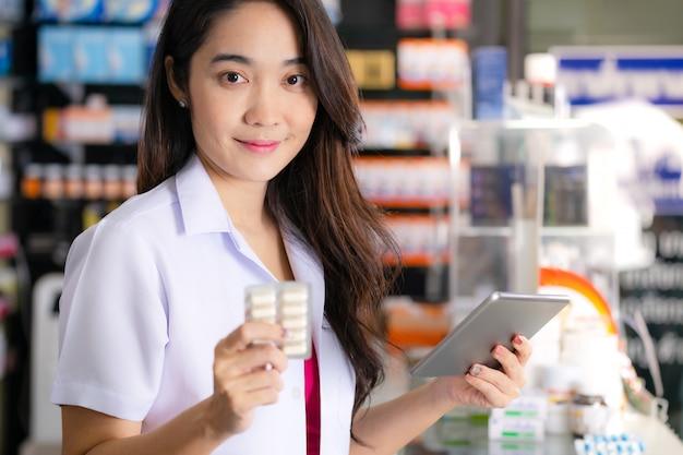 De vrouwelijke apotheker houdt geneeskundedoos geneeskunde en gebruikt digitale tablet in de apotheek