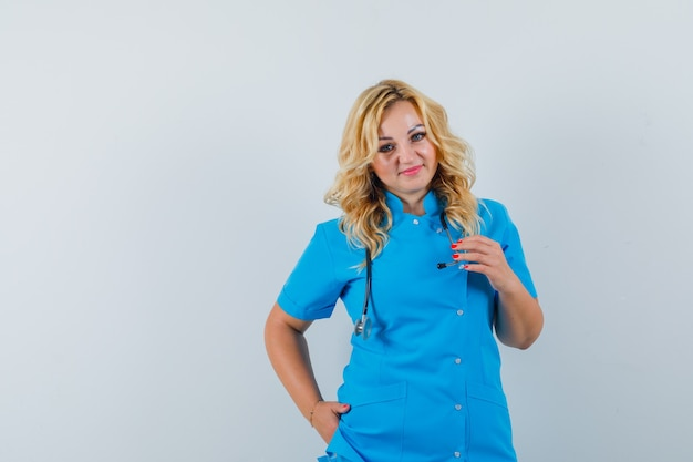De vrouwelijke arts die camera bekijkt met dient zak in blauw uniform in en kijkt tevreden, ruimte voor tekst