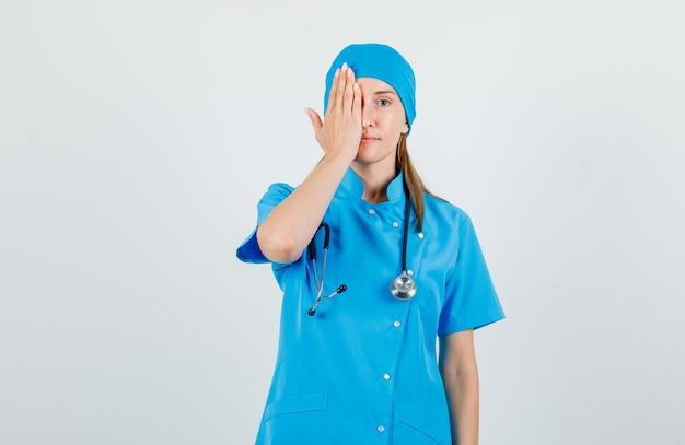 De vrouwelijke arts die één oog behandelt dient blauw uniform in en kijkt positief. vooraanzicht.