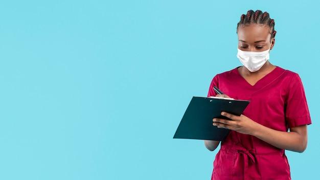 De vrouwelijke arts die masker draagt en schrijft op klembord