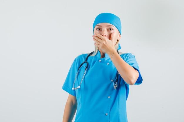 De vrouwelijke arts die mond behandelt met dient blauw uniform in en vergeetachtig kijkt