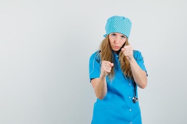 De vrouwelijke arts die zich in bokser bevindt stelt in blauw uniform en kijkt zelfverzekerd