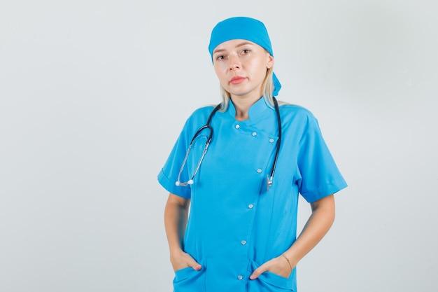 De vrouwelijke arts die zich met handen in zakken in blauw uniform bevindt en ernstig kijkt