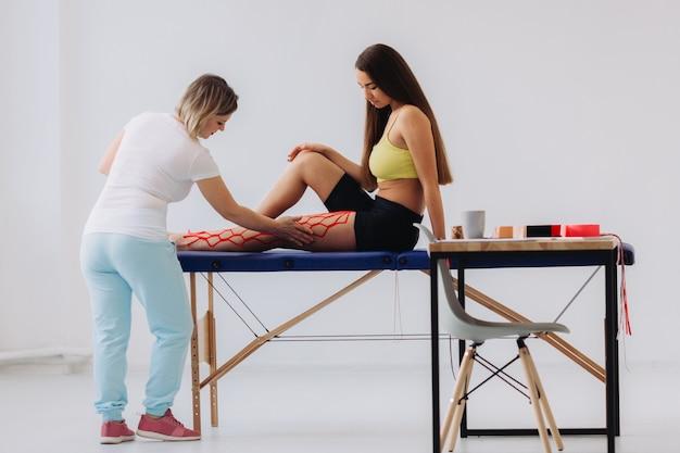 De vrouwelijke arts helpt vrouw door kinesiotape op haar been te zetten. jonge kaukasische vrouw met kinesiologie elastische therapeutische tape op haar been