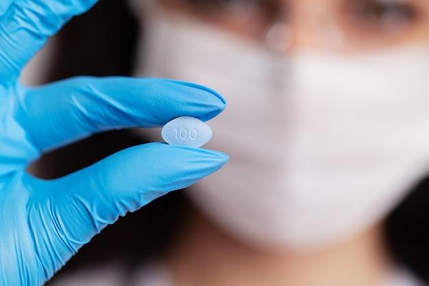 De vrouwelijke arts in handschoenen houdt pillen voor de seksuele gezondheid van mensen