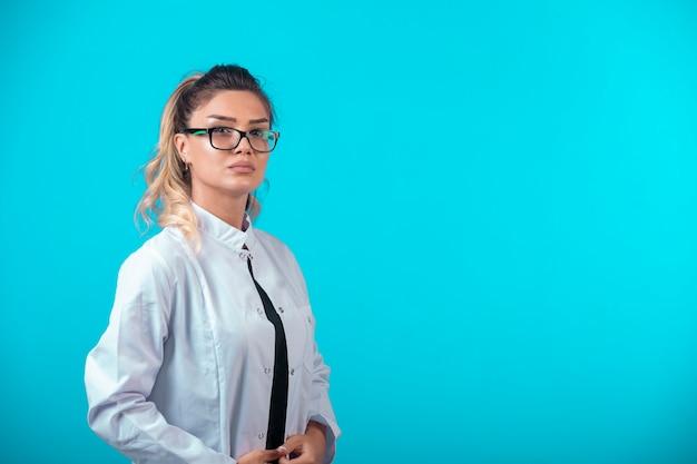De vrouwelijke arts in wit uniform ziet er zelfverzekerd uit.